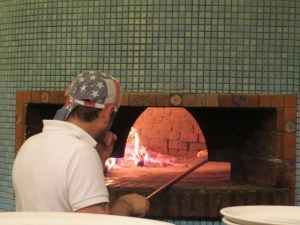 A pizzaiolo deftly turns a pie. I timed them: 3 to 4 minutes to cook a pizza. Must be a bout 1,000 degrees in there.