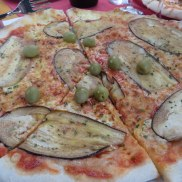 Ric's choice, with thinly sliced eggplant, green olives, and a generous slice of my pizza too.